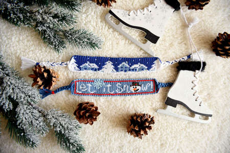 Woven friendship bracelets with alpha patterns Snowy night with houses and Let it snow. Handmade of thread, on  background with spruce cones, Christmas tree toys, fir branches. DIY New Year gift idea