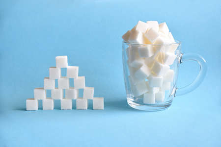 Transparent mug full of refined white sugar cubes and pyramid made from cubes of white sugar on blue background. Copy space