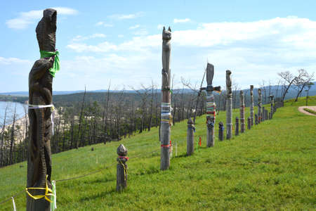 Olkhon, Irkutsk oblast, Russia - 23 July 2021:Fence made of wooden hitching posts with ribbons of shamanism religion in Khuzhir, island Olkhon.