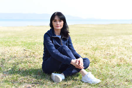 45 y.o. Russian woman sitting and enjoying nature at the beach of Japanese sea.