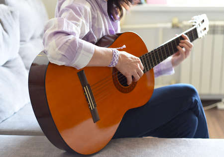 Russian woman playing guitar, sitting on a sofa at home.
