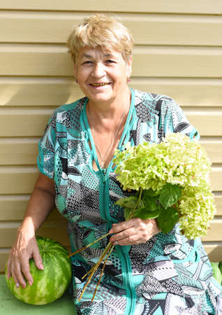 Portrait of 69 y.o. woman sitting on a bench and holding watermelon and bouquet of hydrangea Zdjęcie Seryjne