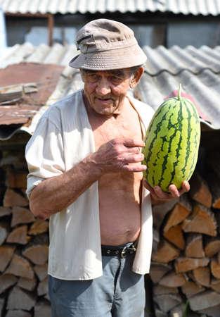 Portrait of an elderly man holding a watermelon