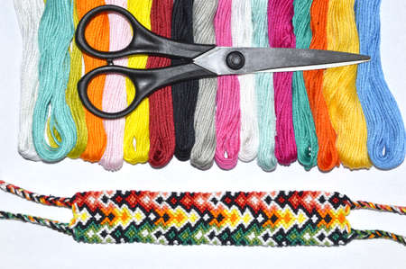 Black scissors on skeins of floss thread near woven friendship bracelet on white background