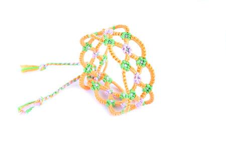 Tied DIY friendship bracelet with unusual braiding pattern on white background Zdjęcie Seryjne