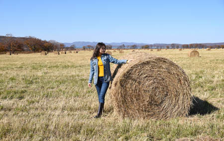 Young brunette woman in denim jacket standing near haystack in field with bales of hay Zdjęcie Seryjne