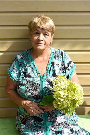 Portrait of 70 y.o. woman sitting on a bench and holding bouquet of hydrangea