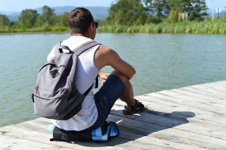 Young man with backpack resting and sitting on pond pier
