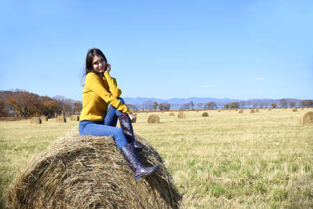 Young brunette woman in yellow sweater and rubber boots sitting on top of haystack in field Zdjęcie Seryjne