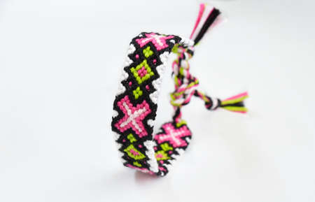 Woven DIY friendship bracelet handmade of embroidery bright thread with knots on white background