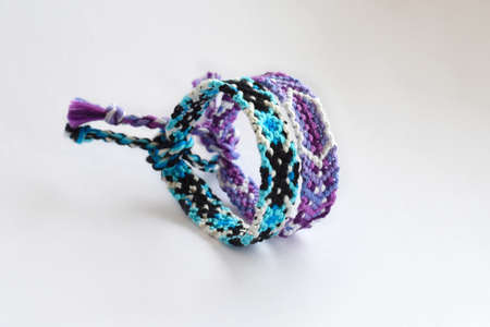 Woven DIY friendship bracelets handmade of embroidery bright thread with knots on white background Zdjęcie Seryjne