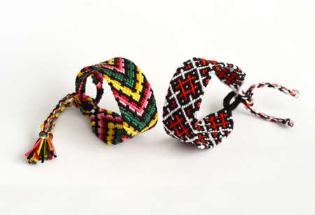 Woven DIY friendship bracelets with bright colorful pattern handmade of thread on white background