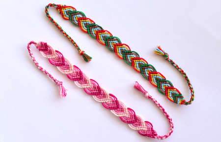 Woven DIY friendship bracelets handmade of embroidery bright thread with knots on white background.