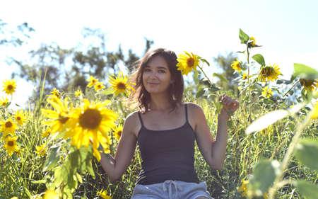 Young girl sitting in a field with sunflowers Zdjęcie Seryjne