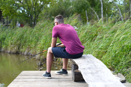 Young fisherman sitting on wooden pier, fishing in the lake. he holding the rod and looking at float