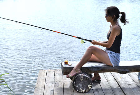 Young fisherman sitting on wooden pier, fishing in the lake.
