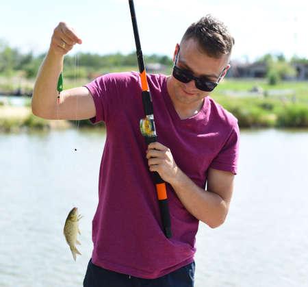 Young fisherman holding crucian carp on fishing rod against a pond Zdjęcie Seryjne