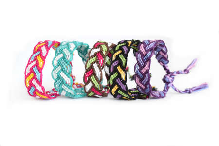 Multicolored woven DIY friendship bracelets Pigtail handmade of embroidery bright thread with knots isolated on white background