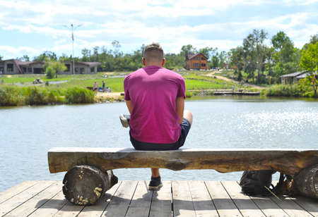 Young man sitting on a bench against lake