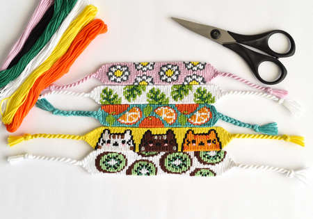 Woven DIY friendship bracelets handmade of embroidery floss with knots, alpha patterns