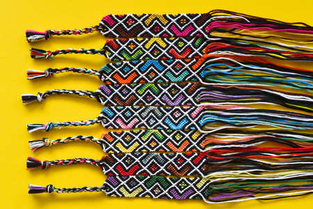 Unfinished DIY woven friendship bracelets with abstract geometric pattern. Summer accessories