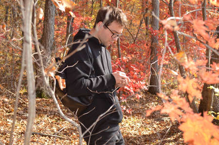 Portrait of Russian young man walking in autumn forest and exploring nature Zdjęcie Seryjne