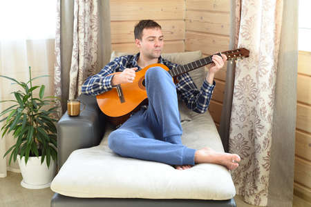 Young man playing guitar and sitting on sofa on weekend morning