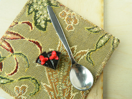 Miniature polymer clay strawberry cake and spoon on wooden surface