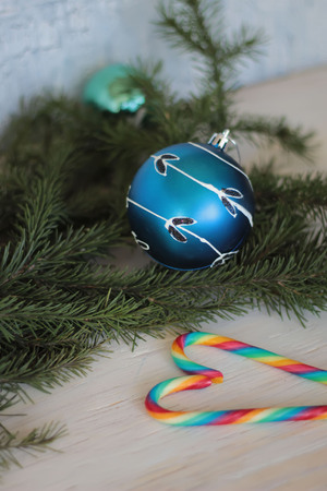 festive decorative blue bauble on christmas tree branch and candy canes