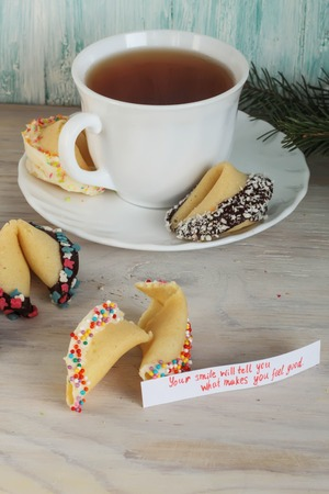 stating: open fortune cookie stating that happy new year and a cup of tea