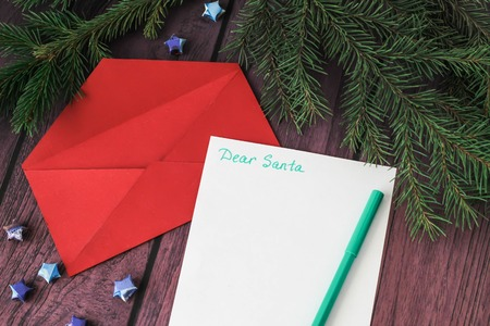 envelope decoration: Empty letter, red envelope and a pen on a wooden background with christmas decoration candy canes, christmas tree