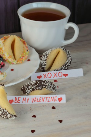 decorated open fortune cookies with blanks xoxo be my valentine and a cup of tea