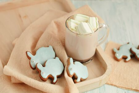 pastry cutters: Homemade Colorful easter cookies hare shaped and a cup of hot chocolate on turquoise wooden board
