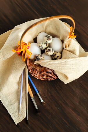 huevos de codorniz: Rustic still life with quail and chicken eggs in a basket ready for decoration on the wooden vintage background for Easter
