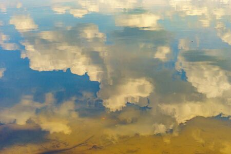 Reflection in the water of the sky and the bottom of the river