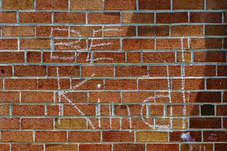 solid background: Red brick wall chalk inscription Be Kind and flag of the USA Stock Photo