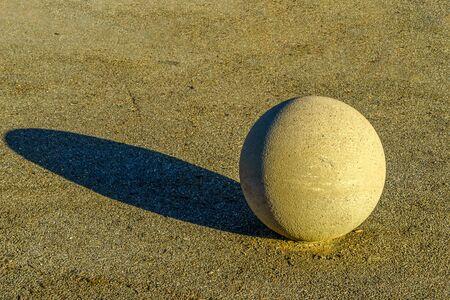 A large stone ball lies on a pavement.