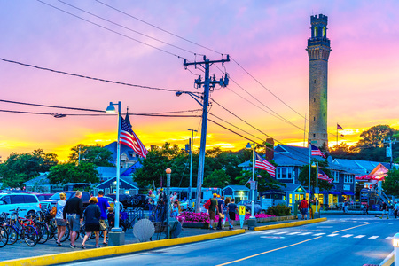 Provincetown, MA, USA - August 12 2017: Bicycle, Pilgrim Monument in the Provincetown Marina during sunset