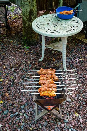 Pieces of raw marinated meat strung on skewers are cooking on a grill. Pieces of raw marinated meat strung on skewers in a blue bowl on a vintage white table.