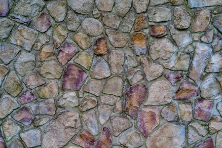 Wall of colored stones fastened with cement, background.