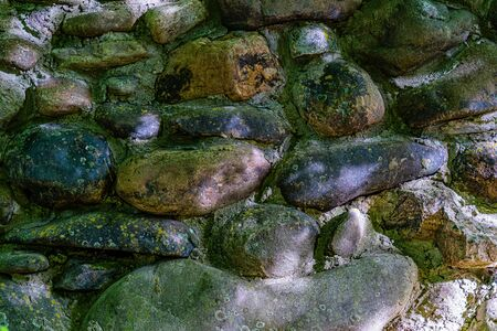 Wall of colored cobblestones fastened with cement, traces of mold, background. Фото со стока