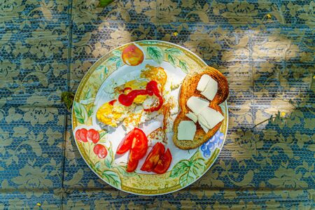 Full breakfast - fried eggs, ketchup, sliced tomato, toasted slice of white bread with slices of butter on a white plate with an ornament on a wooden table covered with a tablecloth, top view. Фото со стока
