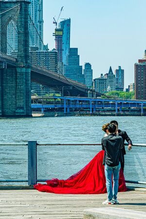 Brooklyn Bridge with lower Manhattan skyline, fashion session with a huge red dress in New York City
