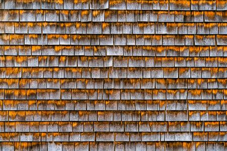 Rough bumpy wood shingles cladding, row of wooden material of small shingles wall facade. Abstract wooden texture