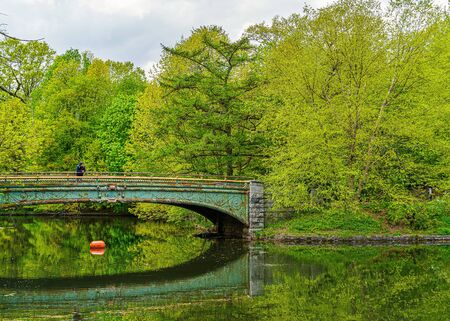 Prospect park, Brooklyn NY May 11, 2020, Brooklyn, New York City. People Keeping Their Social Distance, Because Of The Covid19 Pandemic, Sunday, Lullwater Bridge, Prospect Park, reflection in water out of focus.