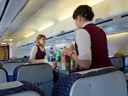 Flight attendants are fed passengers during flight Редакционное
