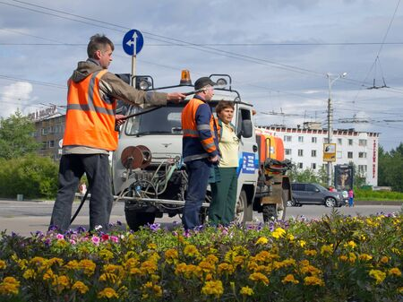 suggests: Murmansk, Russia - June 21, 2013, Employees of urban utilities watering the lawn on the square in the city of Murmansk