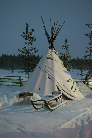 saami: Sami tent and standing next to the sled during the polar night Stock Photo