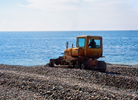 equate: Tractor leveled gravel beach before swimming season Stock Photo