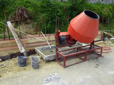site preparation: Preparation of the solution using a concrete mixer on a small construction site Stock Photo
